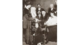 A British woman with her child, casting her vote for the first time in the General Election 1918.