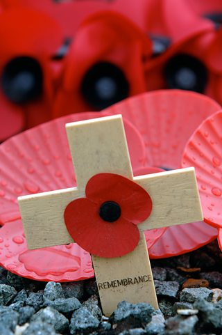 Paper poppy attached to a small wooden cross