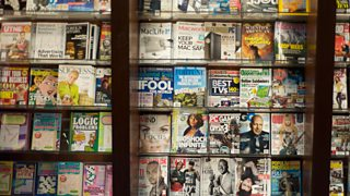 Lots of magazine covers on a magazine stand.