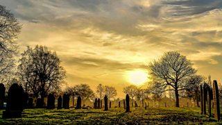Sun setting on a graveyard in autumn.