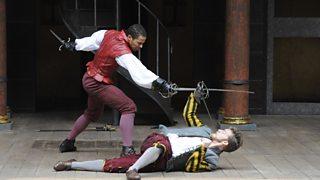 Mercutio lies on the ground while sword-fighting wih Tybalt