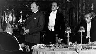 Photo from British premiere of An Inspector Calls. Inspector Goole interrogates Mr Birling with Eric and Gerald looking on (1946).