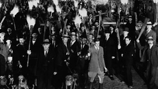 An angry mob, from the 1931 film 'Frankenstein'. A crowd is gathered, and many men are brandishing flaming torches