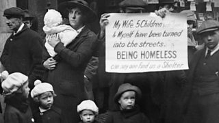 A photo of a destitute family in London in 1919. They are holding a sign asking for help