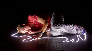 Photo from a stage production of Curious Incident of the Dog in the Night-Time with Christopher Boone laying on an outline of dog