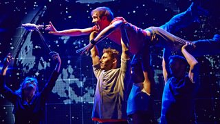 Photo from a stage production of Curious Incident of the Dog in the Night-Time with Christopher Boone being held by the ensemble cast as he tries to rescue his rat