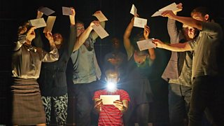 Photo from a stage production of Curious Incident of the Dog in the Night-Time with Christopher Boone surrounded by the ensemble cast with letters