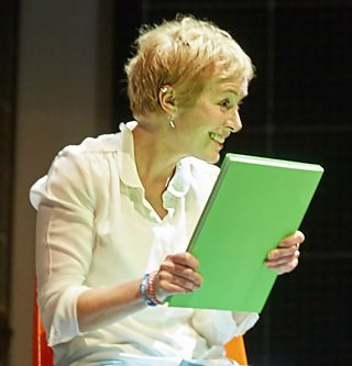 Photo from a stage production of Curious Incident of the Dog in the Night-Time showing Siobhan holding Christopher's note book