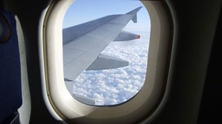 View of sky and aeroplane wing from plane window