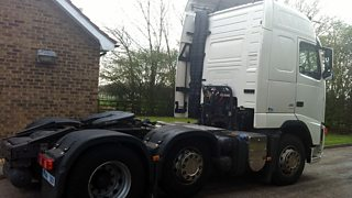 White lorry cab outside a house