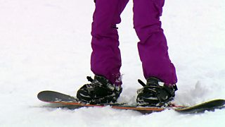 Feet and board of snowboarder standing in the snow