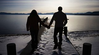 A couple holding hands on a pier of a lake