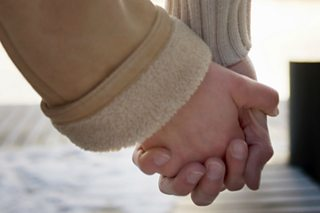 A close-up of a couple holding hands