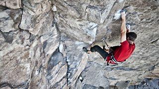 A climber, climbing up a jagged cliff