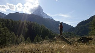 A man standing at the foot of a mountain