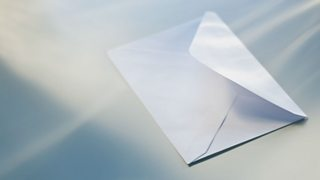 A open white envelope with light shining from it