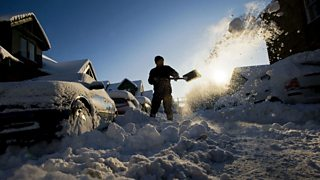 A man clearing deep snow from a road