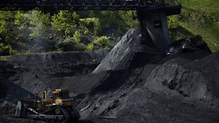 Bulldozer moving heaps of coal - as a fossil fuel, it is a non-renewable energy source