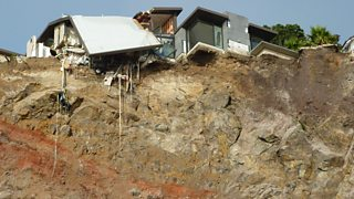 An earthquake-damaged home stands at the edge of a cliff in Christchurch