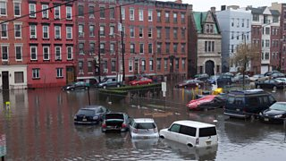 Cars sit submerged in water on a flooded street in Hoboken, New Jersey