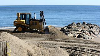 A bulldozer moves sand up the beach