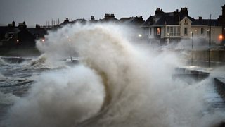Waves crash against a seawall