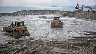 Bulldozers moving sand during beach nourishment
