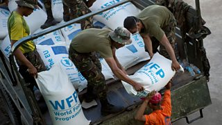 Philippines armed forces and volunteers unload sacks of rice