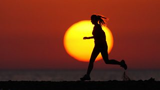 20-year-old woman doing long-distance running on the beach at sunset