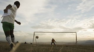 A footballer shoots towards the goal