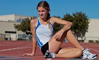 A female athlete stretches before a race