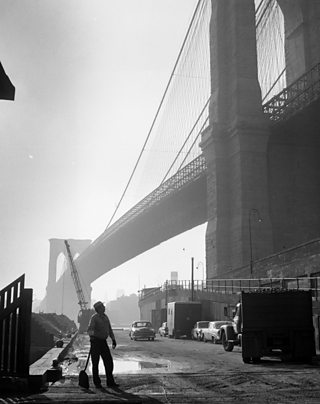 A dockhand pauses whilst shovelling coal onto a truck under Brooklyn Bridge, New York