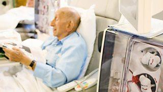 An elderly man receiving treatment in a hospital ward