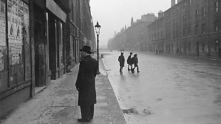 A man looking at a boarded up shop in the Gorbals area of Glasgow in the 1930s