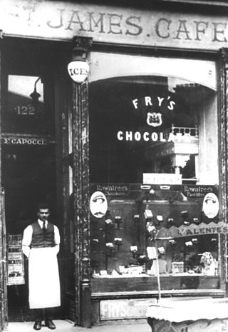 Italian café owner standing outside his Glasgow shop in the 1930s