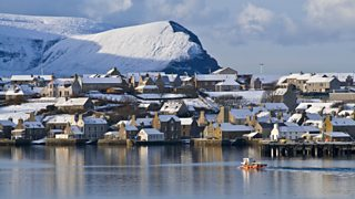 Stromness Harbour in Orkney with a fishing boat leaving harbour in winter