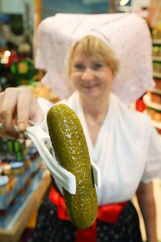 A woman in traditional dress presents a gherkin from the Spreewald region