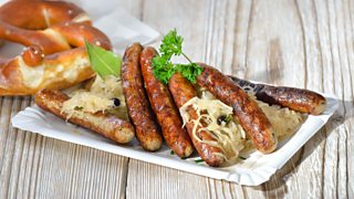 Six fried Bavarian sausages from Nuremberg - so called 'rostbratwurst' - served with sauerkraut and a pretzel
