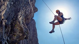 Young woman abseiling from a steep rock, just in front of the sun