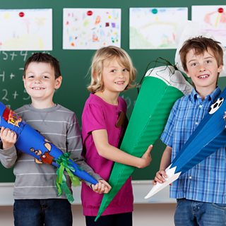Children holding decorative cones in school