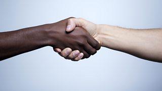 Interracial handshake on gray background