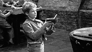 Mark Lester playing Oliver Twist holds up an empty bowl in the 1968 film adaptation of the Charles Dickens' novel