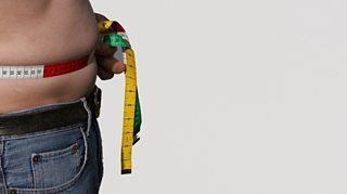 Overweight man measuring his waist