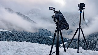 Two tripods extended on a mountainside