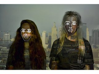 Student experimental portrait photograph with projected skyline and digitally-drawn faces superimposed on models