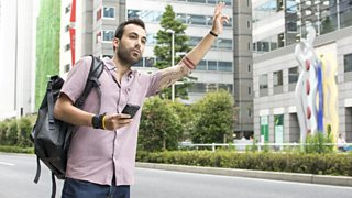 Young man holding phone hailing Uber taxi
