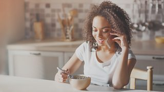 Woman eating breakfast in kitchen while talking on her smart phone