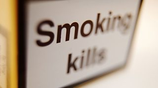 Close-up of an open packet of cigarettes showing 'Smoking kills' warning