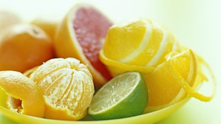 Citrus fruits on a plate, including a lime, a lemon and a pink grapefruit