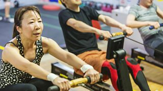 A woman exercising on an indoor rowing machine
